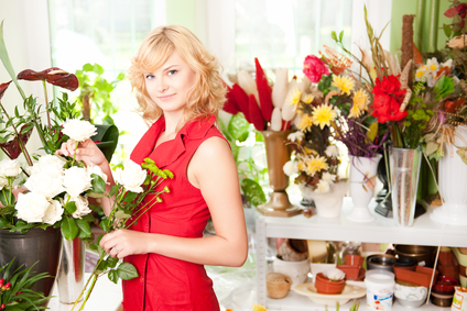 In a flower shop, holding flowers and smiling